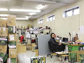 うず高く積まれたキャンプ用品に囲まれた福島さんの仕事場